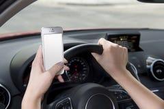 Mano de la mujer que sostiene el volante y el teléfono móvil que conducen el coche mientras que manda un SMS distraído en riesgo imagen de archivo libre de regalías