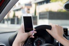 Mano de la mujer que sostiene el volante y el teléfono móvil que conducen el coche mientras que manda un SMS distraído en riesgo fotografía de archivo libre de regalías
