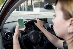 Mano de la mujer que sostiene el volante y el teléfono móvil que conducen el coche mientras que manda un SMS distraído en riesgo fotos de archivo libres de regalías
