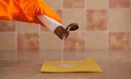 Mano de la mujer que sostiene la esponja amarilla y que vierte el líquido de la limpieza en él Economía doméstica y concepto de l Fotografía de archivo