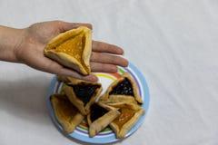 Mano de la mujer que sostiene la galleta del hamantash encima de la placa colorida con m?s galletas del hamantash imagenes de archivo
