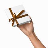 Mano de la mujer que sostiene la actual caja blanca del día de fiesta con la cinta de oro anaranjada Fotos de archivo libres de regalías
