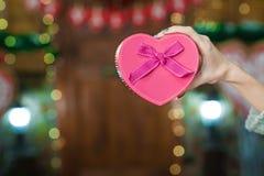 Mano de la mujer que sostiene la caja rosada bajo la forma de corazón Imagen de archivo libre de regalías