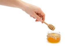 Mano de la mujer que sostiene la cuchara de la miel Imagen de archivo libre de regalías