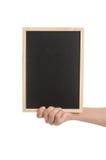 Mano de la mujer que sostiene la pizarra en el fondo blanco Foto de archivo libre de regalías