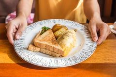 Mano de la mujer que sostiene la placa blanca con la patata de la tortilla, tomates perejil y queso feta y pan en la tabla de mad Fotos de archivo
