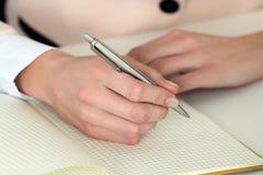 Mano de la mujer que sostiene la pluma de plata lista para hacer la nota en noteb abierto Fotos de archivo libres de regalías