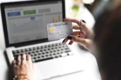 Mano de la mujer que sostiene la tarjeta de crédito del platino con el fondo del ordenador portátil imagen de archivo