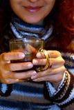 Mano de la mujer que sostiene la taza de té, fondo de la falta de definición Fotos de archivo