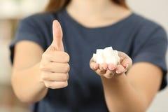 Mano de la mujer que sostiene los cubos del azúcar con los pulgares para arriba Fotos de archivo