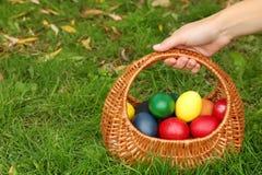 Mano de la mujer que sostiene los huevos de Pascua en cesta Imagen de archivo libre de regalías