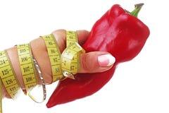 Mano de la mujer que sostiene la paprika roja de la pimienta de la dieta en fondo blanco aislado del recorte Foto del estudio con Imagenes de archivo