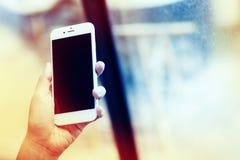 Mano de la mujer que sostiene smartphone contra en liso en la cafetería c Foto de archivo libre de regalías