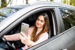 Mano de la mujer que sostiene smartphone en ventana su coche Imagen de archivo libre de regalías