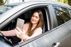 Mano de la mujer que sostiene smartphone en ventana su coche Fotografía de archivo libre de regalías