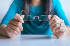 Mano de la mujer que sostiene sus lentes sucias fotos de archivo libres de regalías