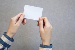 mano de la mujer que sostiene la tarjeta en blanco en fondo gris foto de archivo libre de regalías