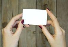Mano de la mujer que sostiene la tarjeta en blanco en la tabla de madera fotos de archivo libres de regalías