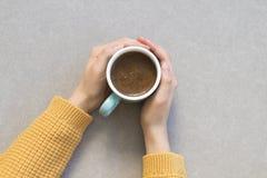 Mano de la mujer que sostiene la taza de café en fondo gris imagen de archivo libre de regalías