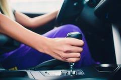 Mano de la mujer que sostiene un engranaje mientras que conduce como un miembro fotos de archivo libres de regalías