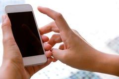 Mano de la mujer que sostiene un teléfono elegante Foto de archivo libre de regalías
