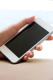 Mano de la mujer que sostiene un teléfono elegante Imagen de archivo libre de regalías