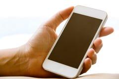 Mano de la mujer que sostiene un teléfono elegante Imagenes de archivo