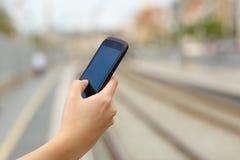 Mano de la mujer que sostiene un teléfono elegante en una estación de tren Fotografía de archivo