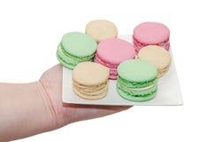Mano de la mujer que sostiene una placa blanca con los macarrones dulces coloreados, f Imágenes de archivo libres de regalías
