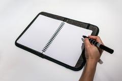 Mano de la mujer que sostiene una pluma para escribir en la página en blanco de los wi de un cuaderno Imágenes de archivo libres de regalías
