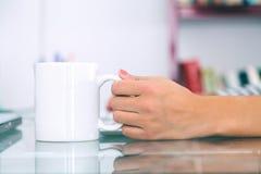 Mano de la mujer que sostiene una taza blanca Imagen de archivo libre de regalías