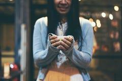 Mano de la mujer que sostiene una taza de té verde Fotografía de archivo libre de regalías