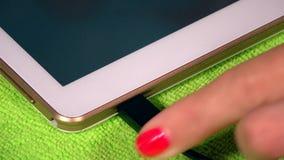 Mano de la mujer que tapa el cable blanco del usb del micrófono a la tableta elegante almacen de video