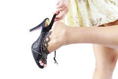 Mano de la mujer que toca su pie en zapatos de los altos talones. imagen de archivo