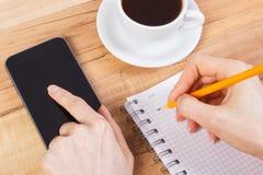 Mano de la mujer que usa el teléfono móvil o el smartphone y escribiendo notas en libreta Fotografía de archivo