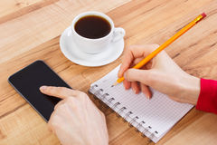 Mano de la mujer que usa el teléfono móvil y escribiendo notas en la libreta, taza de café Imágenes de archivo libres de regalías