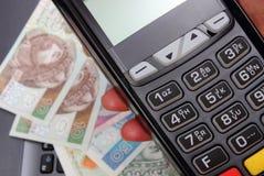 Mano de la mujer que usa el terminal del pago, dinero polaco de la moneda en el ordenador portátil Fotos de archivo