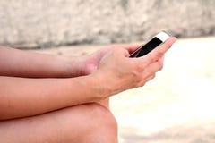 Mano de la mujer que usa los teléfonos elegantes móviles Fotografía de archivo
