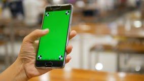 Mano de la mujer que usa smartphone móvil con el monitor verde en blanco de la pantalla y siguiendo la marca para el uso y la tec almacen de video