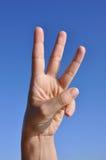 Mano de la mujer: tres dedos para arriba imagen de archivo