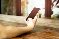 Mano de la mujer usando el teléfono celular Imágenes de archivo libres de regalías