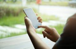 Mano de la mujer usando el teléfono celular Foto de archivo