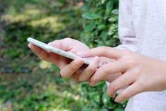 Mano de la mujer usando el teléfono elegante en fondo verde del parque Foto de archivo