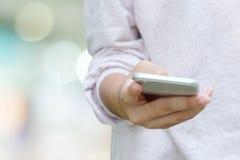 Mano de la mujer usando el teléfono elegante sobre fondo del bokeh de la falta de definición Fotos de archivo
