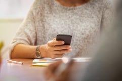 Mano de la mujer usando el teléfono móvil fotos de archivo