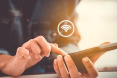 Mano de la mujer usando smartphone con el icono del wifi foto de archivo