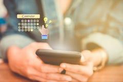 Mano de la mujer usando smartphone hacer el planeamiento al uso digital del calendario fotografía de archivo libre de regalías
