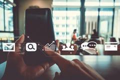 Mano de la mujer usando smartphone o la tableta e iconos de la comunicación stock de ilustración