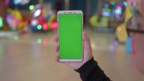 Mano de la mujer usando un smartphone con la pantalla verde en el centro comercial almacen de video