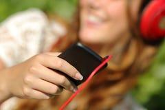 Mano de la mujer usando un teléfono elegante a escuchar la música con los auriculares Fotos de archivo